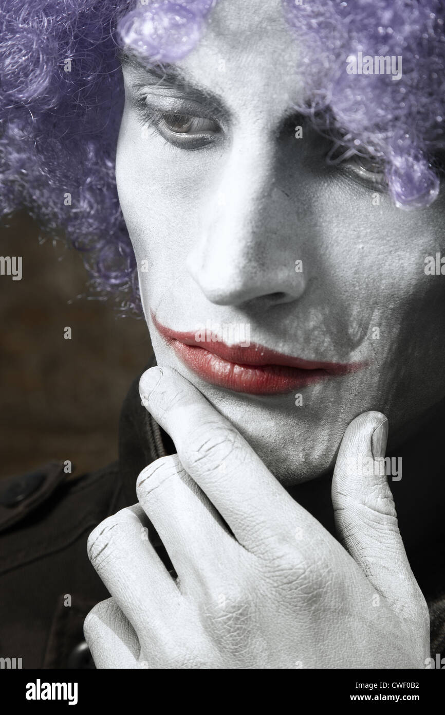 Single sad funny man with theatrical makeup and wig. Vertical photo with dramatic colors and toning - Stock Image