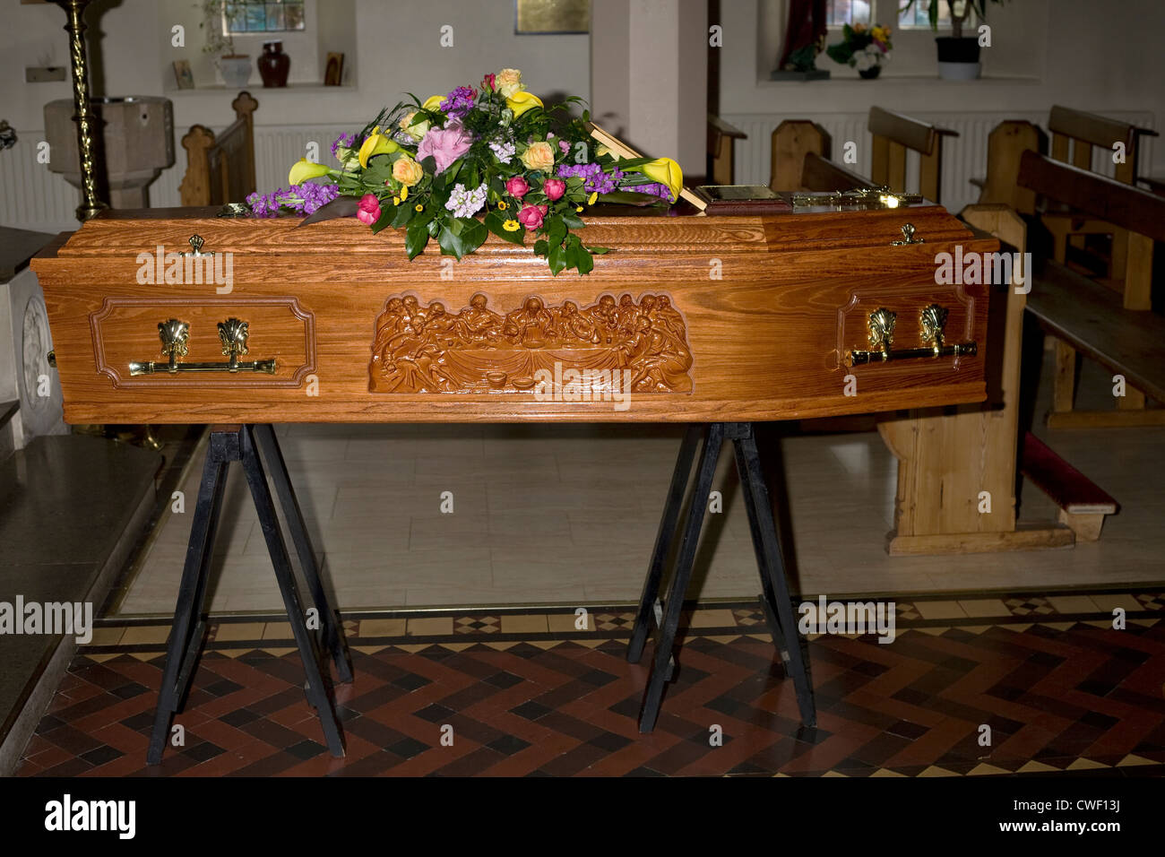 A wooden coffin with last supper design and flowers on top resting in church ready for the occupant's funeral - Stock Image
