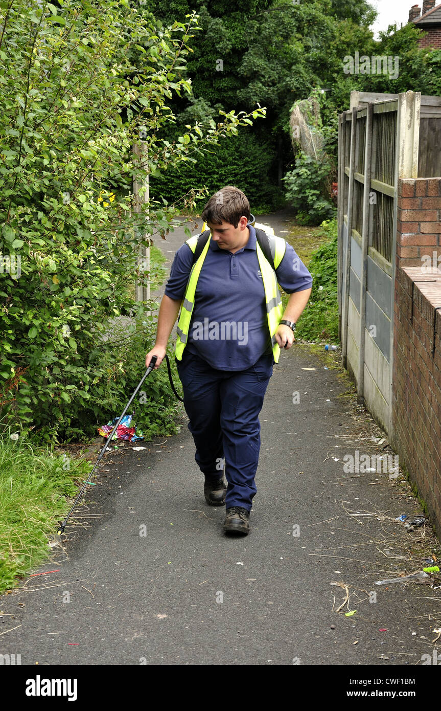 Manchester city council employee uses a hand operated back pack sprayer on edge of footpath - Stock Image