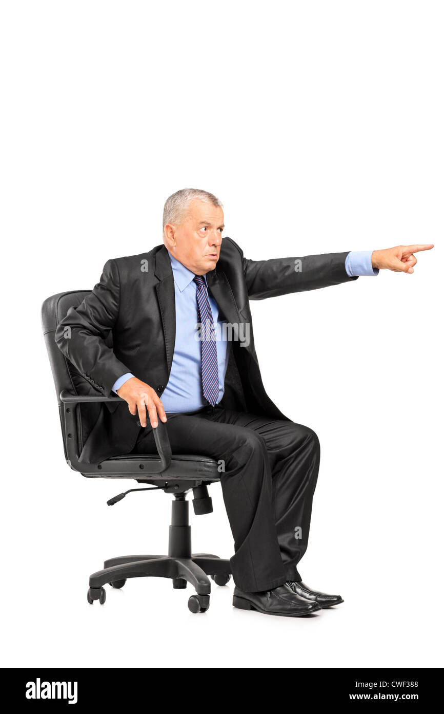Angry boss sitting in armchair and pointing his finger isolated on white background - Stock Image
