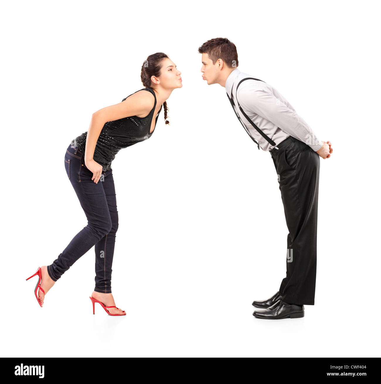Full length portrait of a young heterosexual couple about to kiss isolated against white background - Stock Image