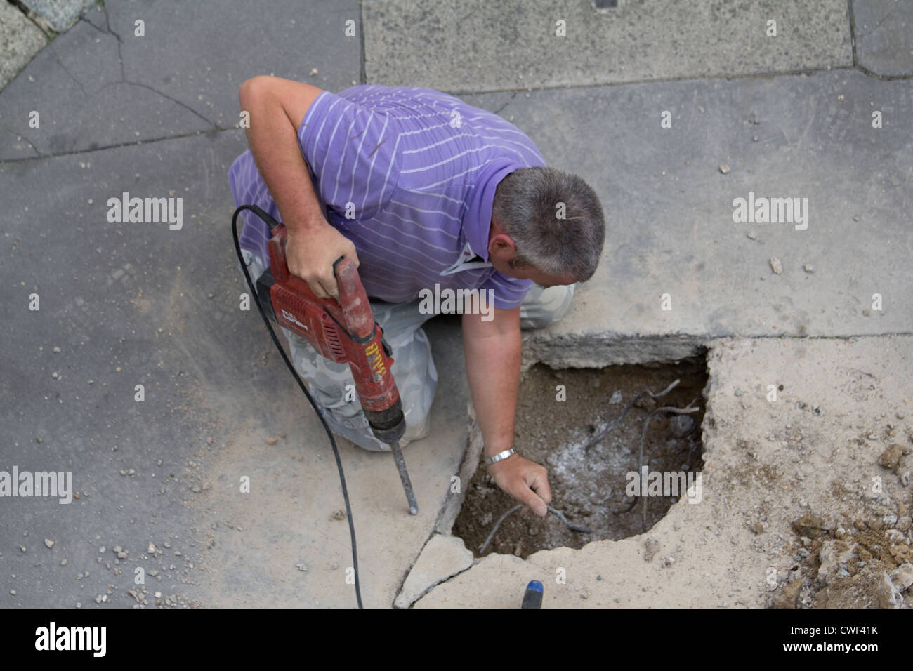 cabling repairs man drilling hole in the pavement City of London - Stock Image