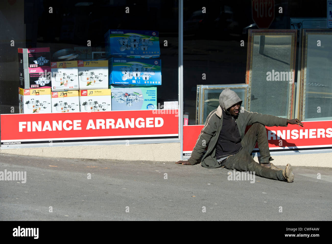 Man bagging sitting on a street in Cape Town, South Africa - Stock Image