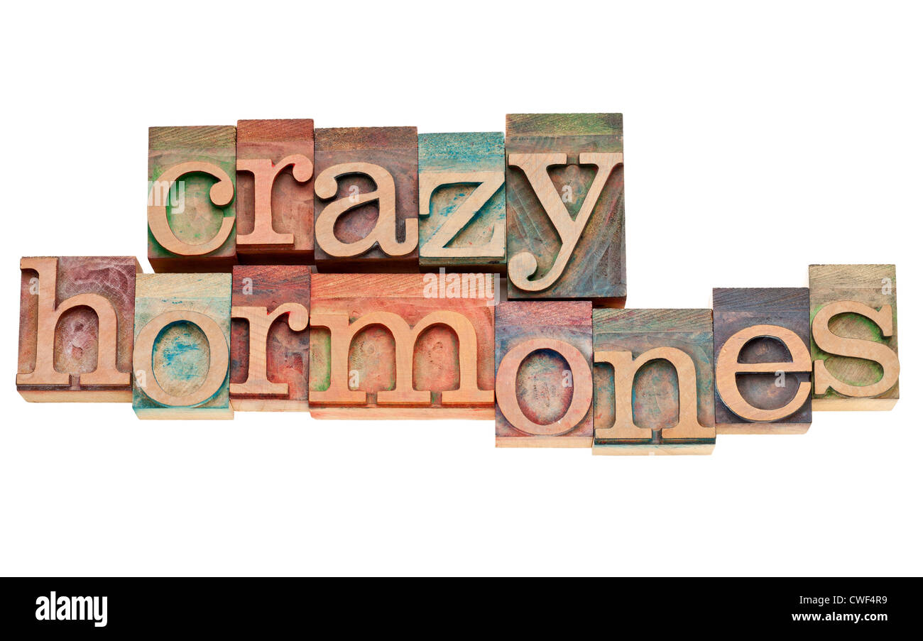 crazy hormones - isolated words in vintage letterpress wood type stained by color inks - Stock Image