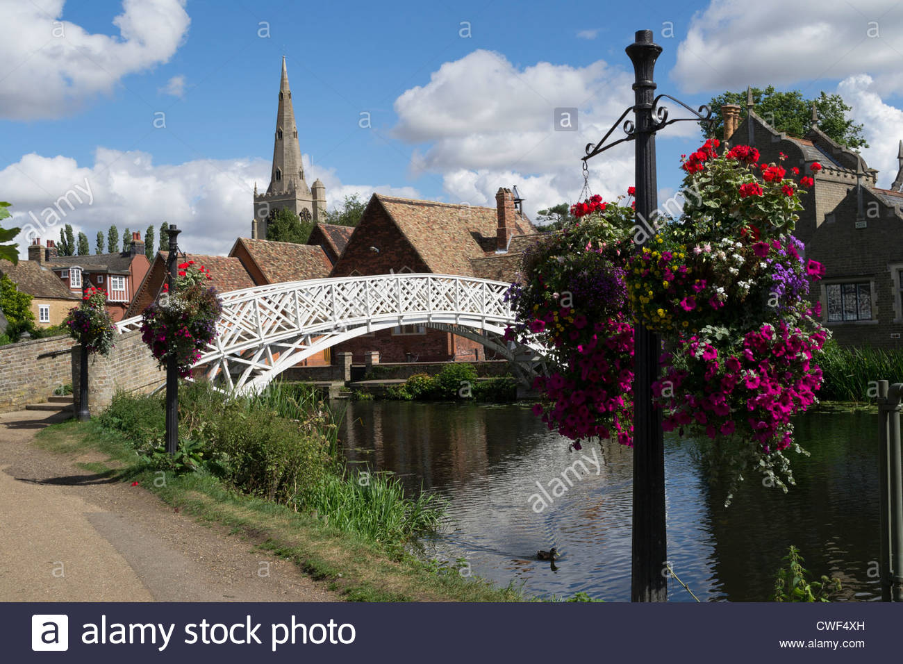 The Chinese Bridge with church spire and hanging baskets in Godmanchester, England - Stock Image