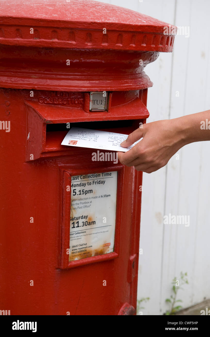 person posting or mailing a holiday post card into a red royal mail post box - Stock Image