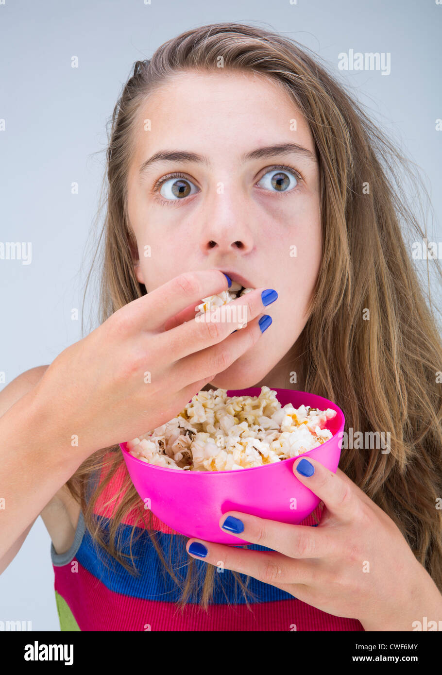 movie use watches television kid on safe the young photo girl popcorn during night sofa lifts eating feet stock child image to