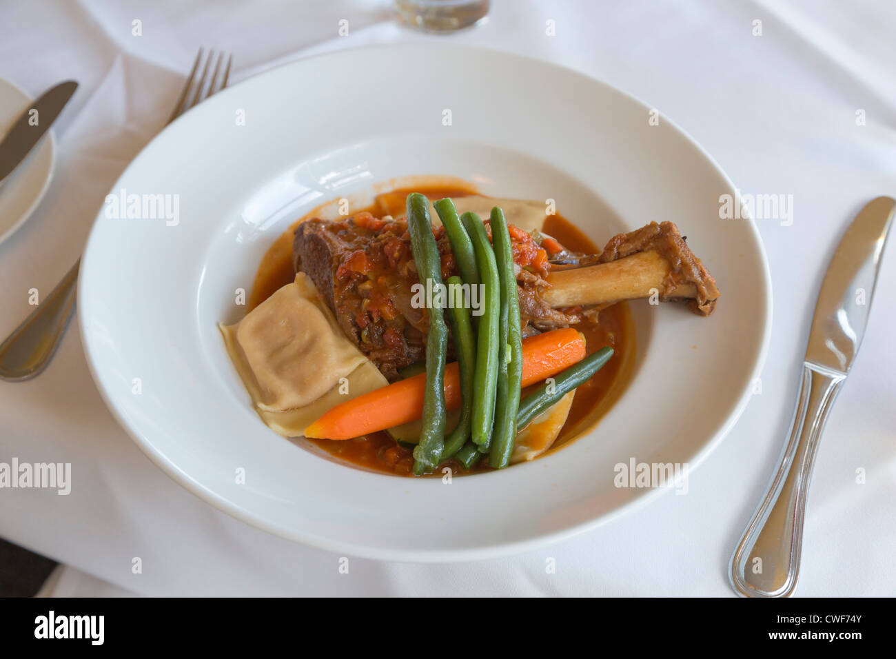 Lamb shank with green beans, carrots and home made pasta - Stock Image