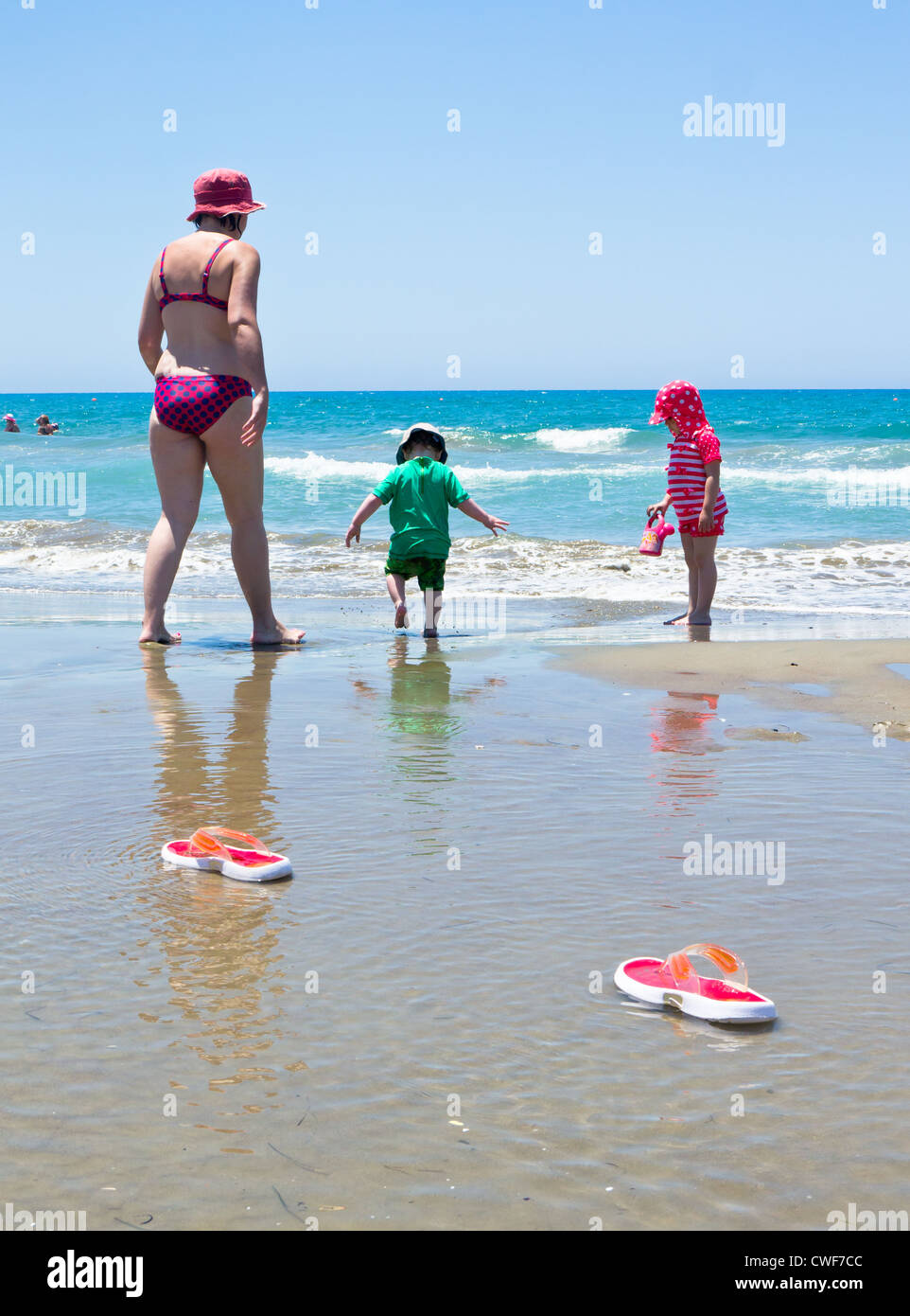 ce9450c7737d30 a mother and two young children paddle barefoot in the sea with flip flops  in the