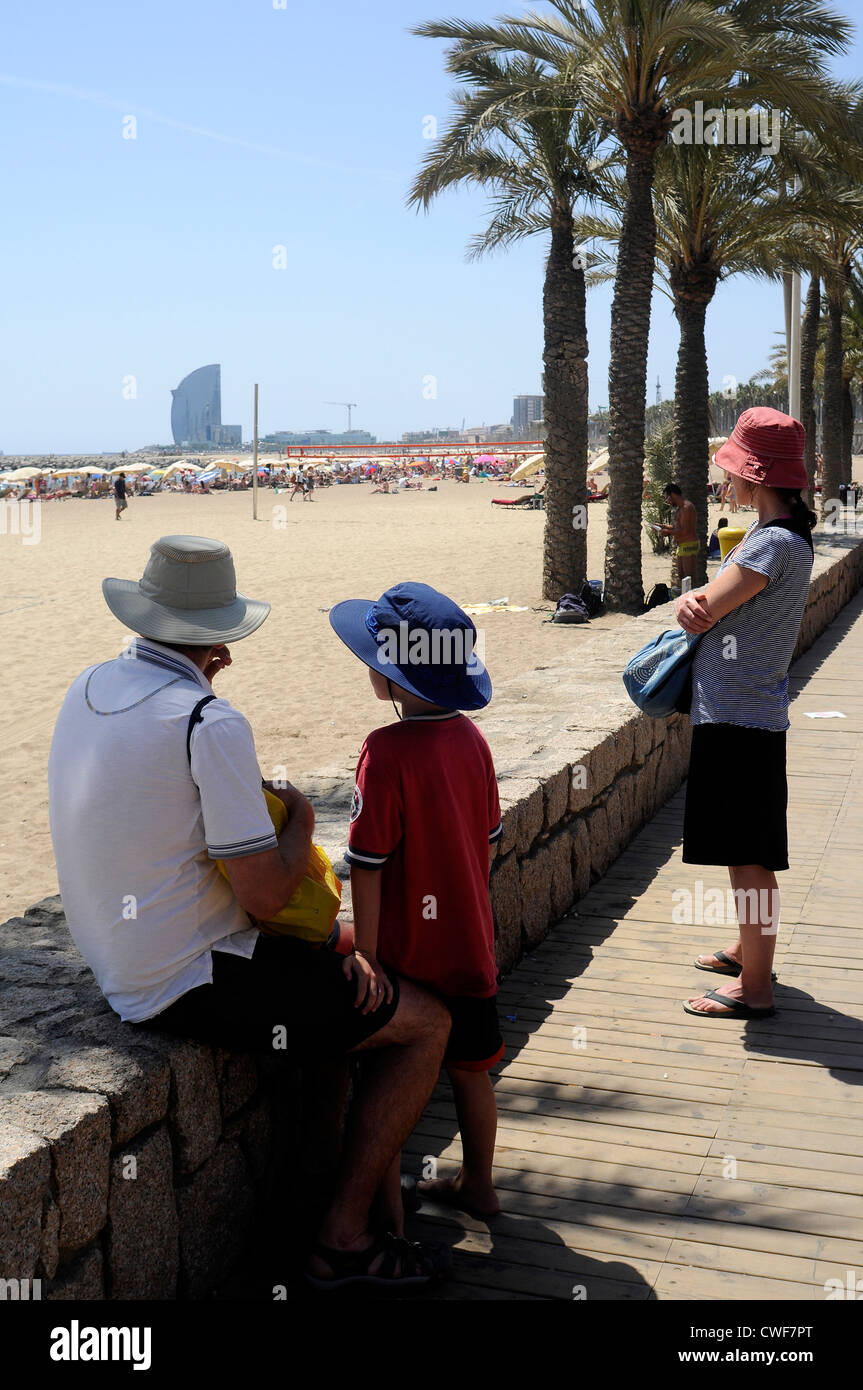 ain Barcelona a family of three members wear hats  while they are looking at the seaside - Stock Image