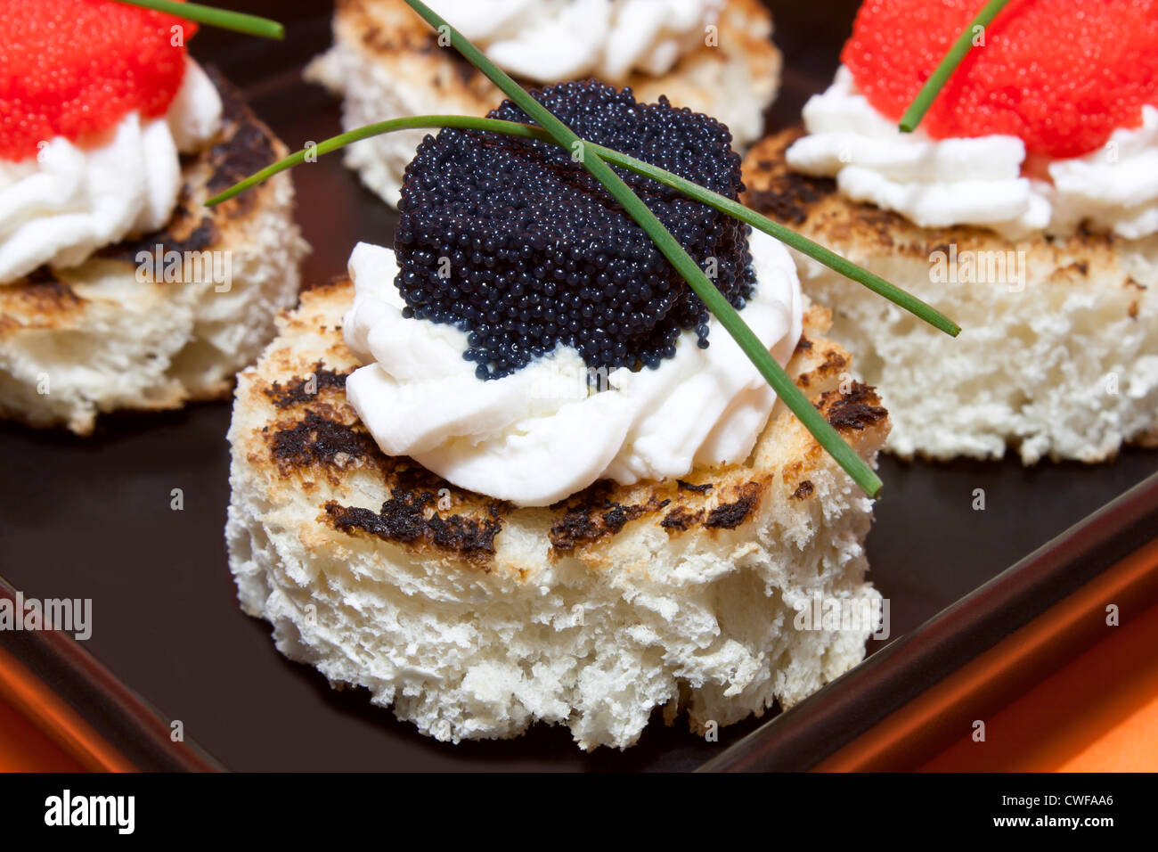 Red and black caviar canapés decorated with chives. - Stock Image