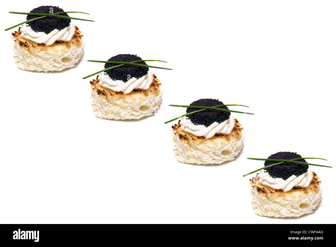 Red and black caviar canapés decorated with chives, on white background. - Stock Image