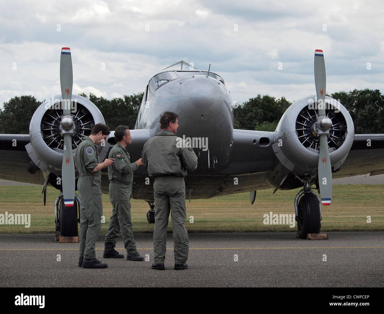 Crew standing by their classic Beechcraft B18S aeroplane at Seppe airfield, the Netherlands - Stock Image