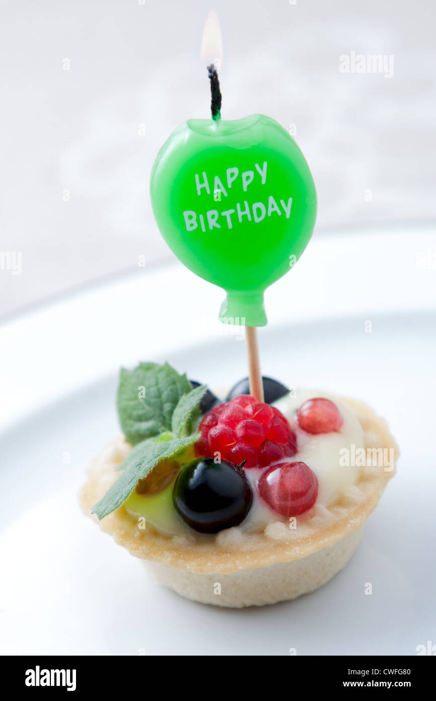 Birthday candle in fruit tart - Stock Image