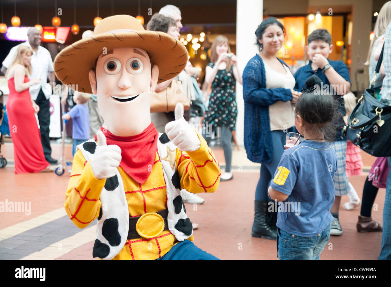 Children's entertainer Woody character from 'Toy Story', Cardiff, Wales. Children with a man dressed - Stock Image