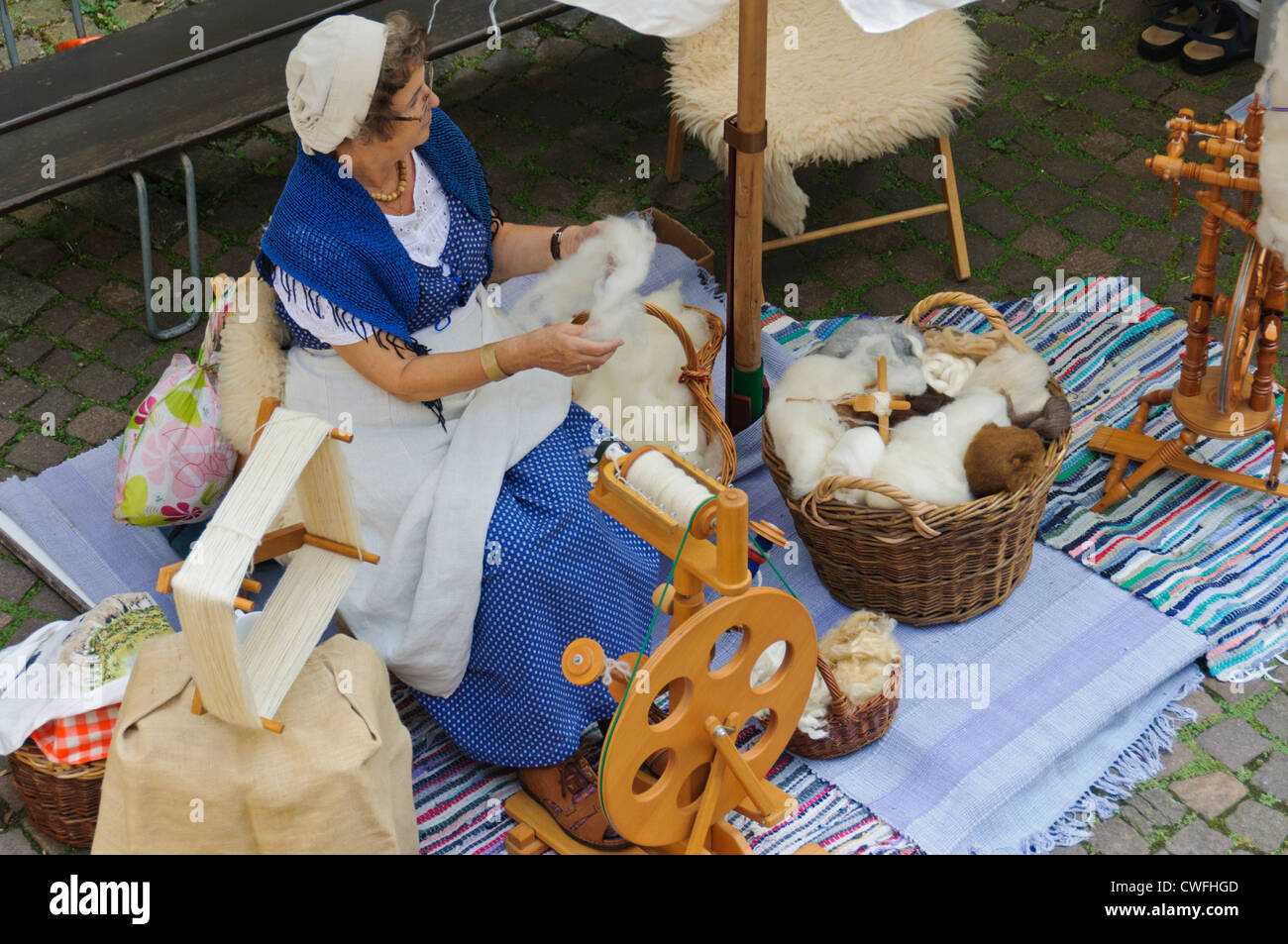 Spinstress in historic costume at a mediaeval market spins raw wool with ancient spinning historical spa Staufer - Stock Image
