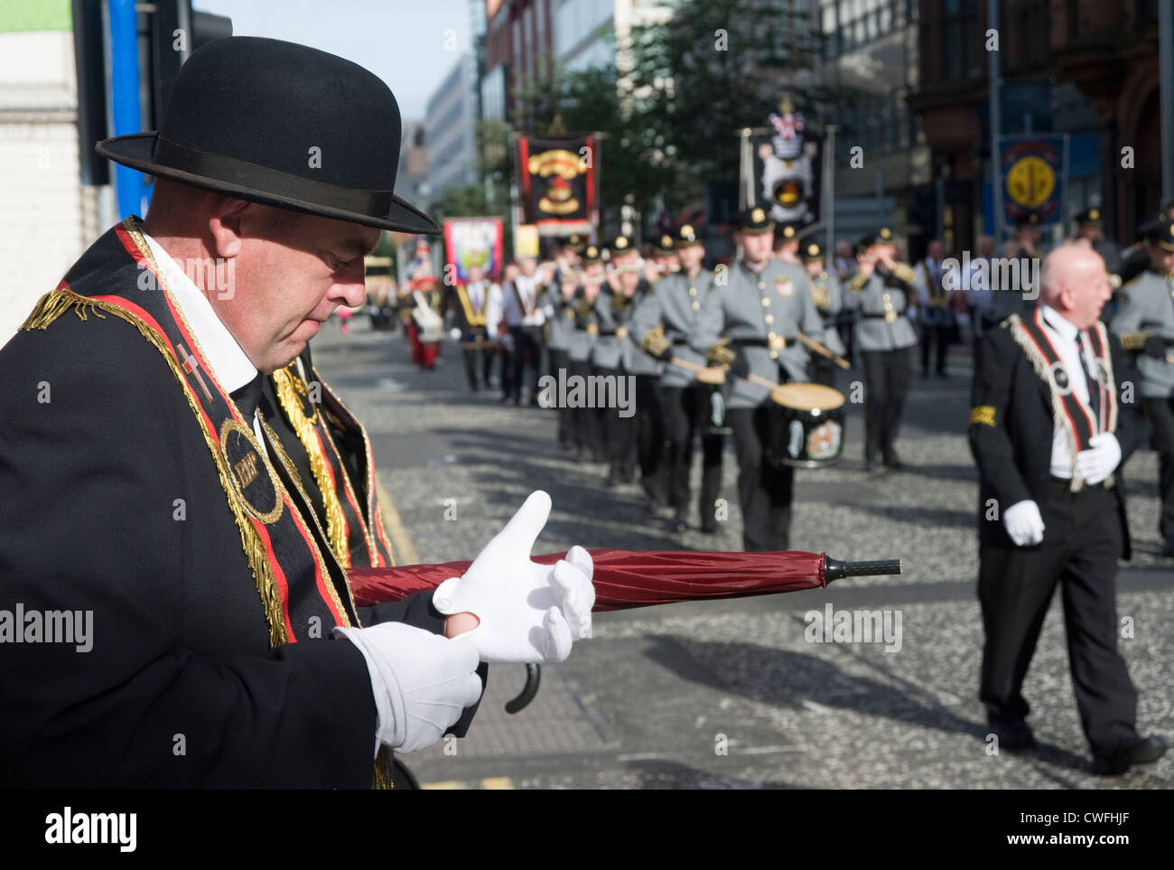 Orangeman adjusts his gloves during a march in Belfast. - Stock Image