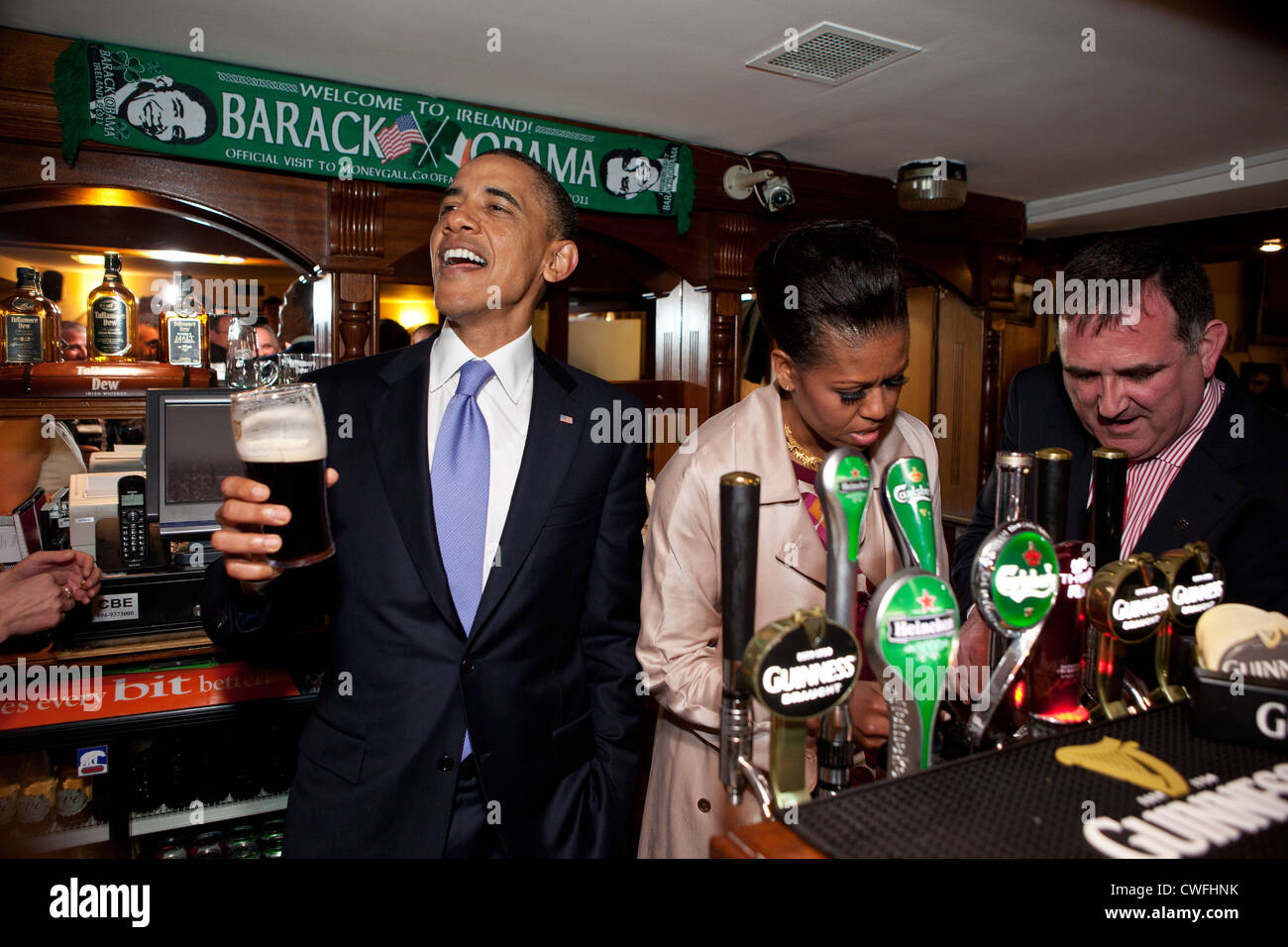 President Barack Obama talks with pub-goers as First Lady Michelle Obama draws a pint at Ollie Hayes pub in Moneygall, - Stock Image