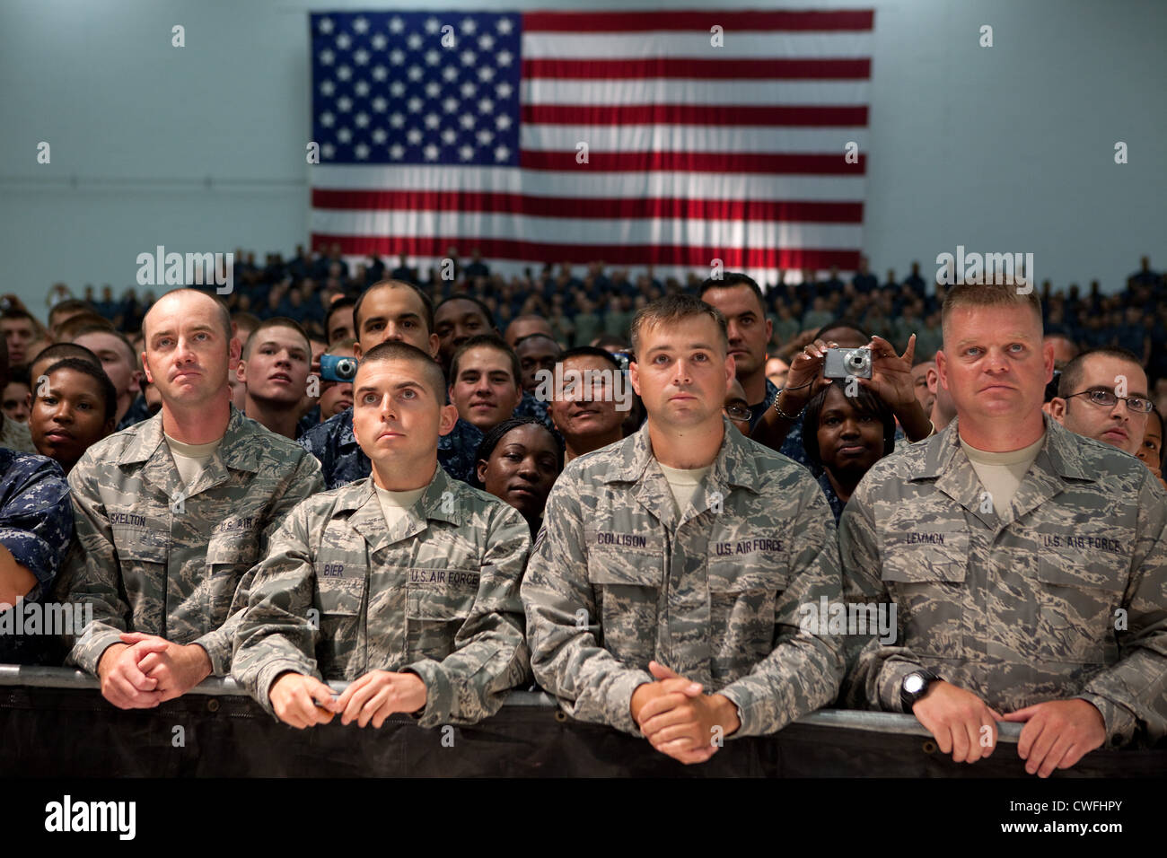 Audience members listen as President Barack Obama delivers remarks during an event with military personnel at the - Stock Image
