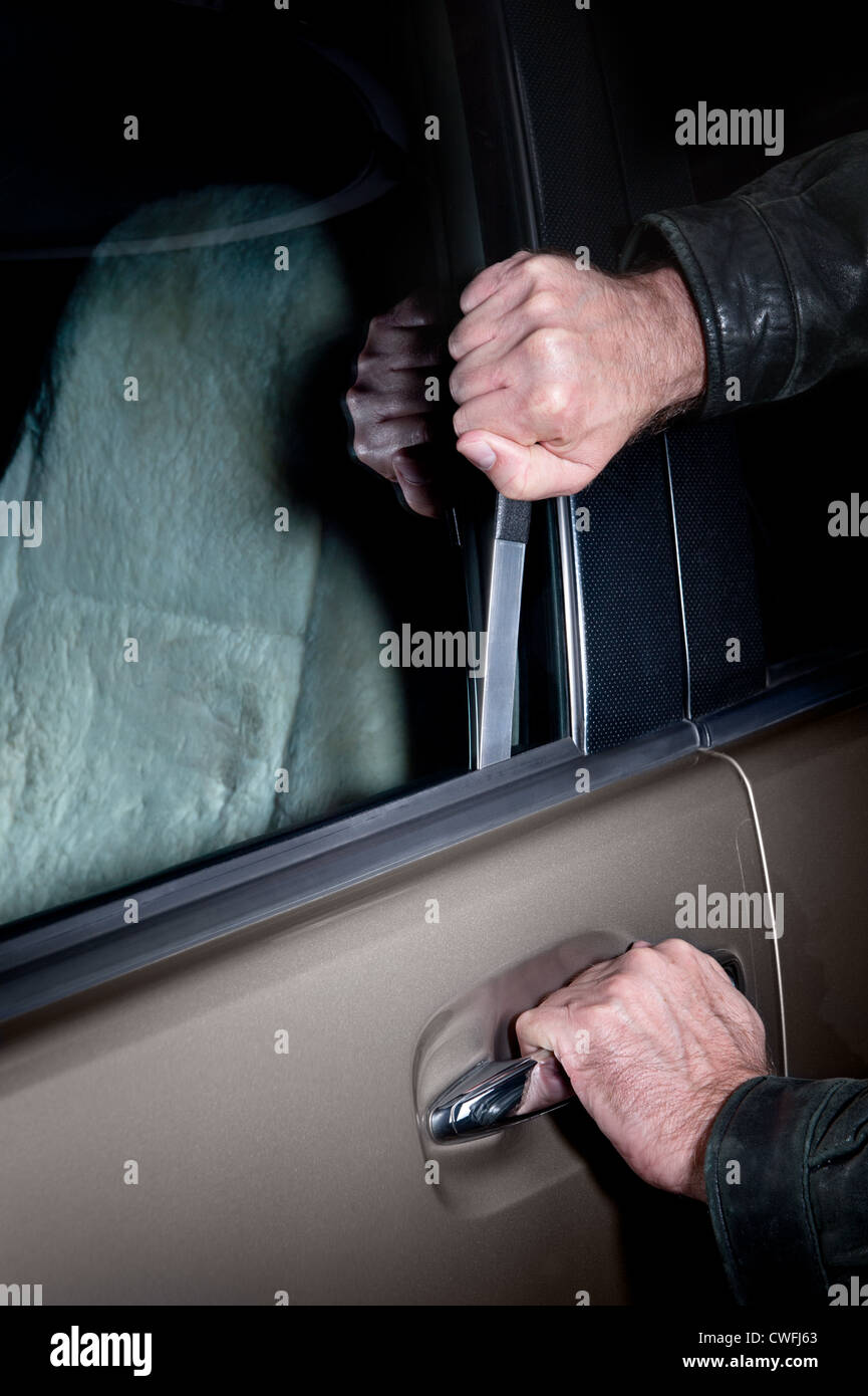 A car thief uses a Slim Jim tool to pop the lock on a car door to steal it. - Stock Image