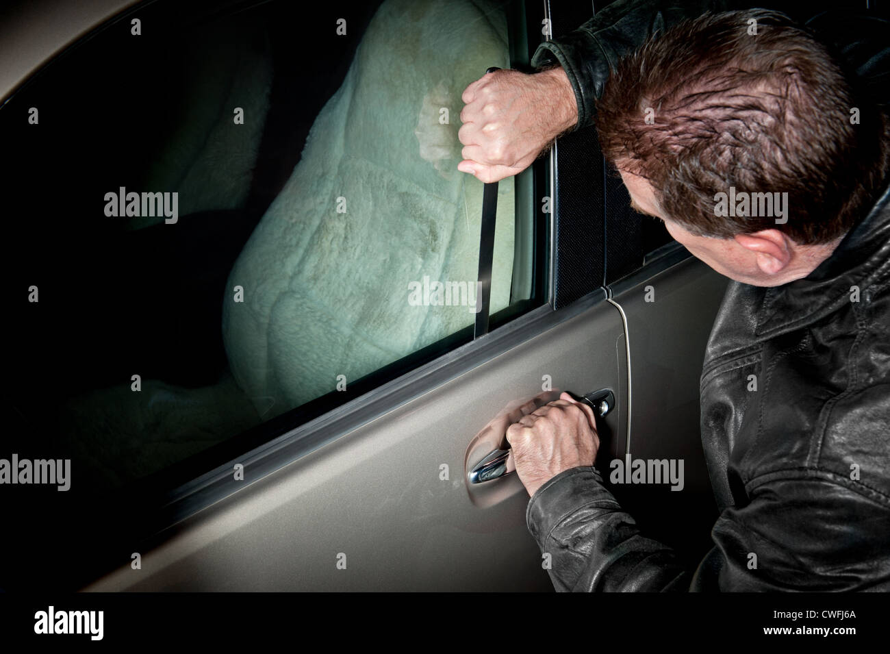 A male car thief uses a flat metal lock pick to break into a vehicle. - Stock Image