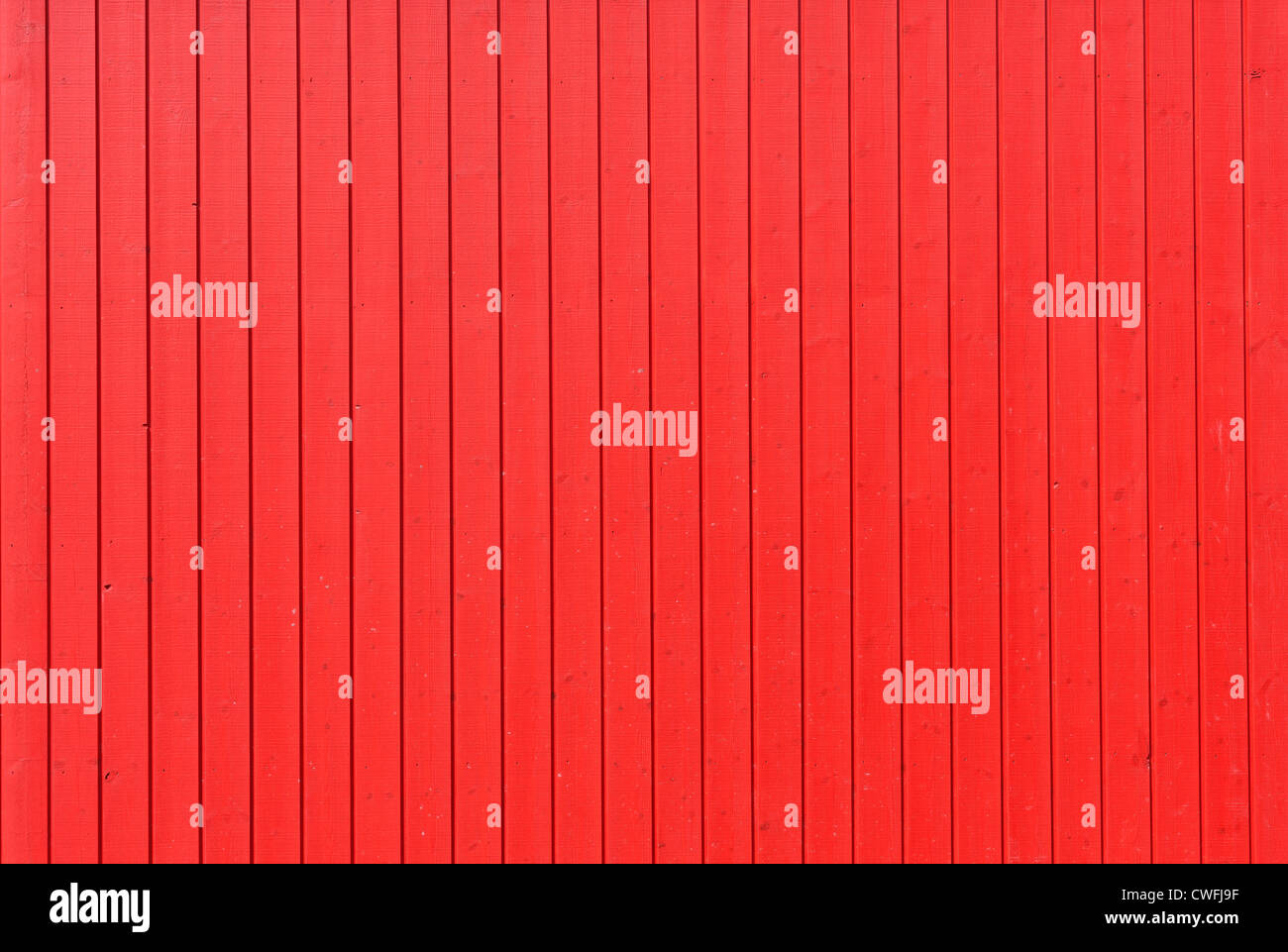 Background image of a wooden wall painted in bright red color - Stock Image