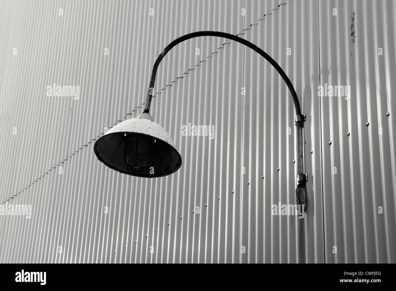 Electric light fixture on wall of a corrugated metal building, Granville Island, Vancouver, British Columbia, Canada - Stock Image