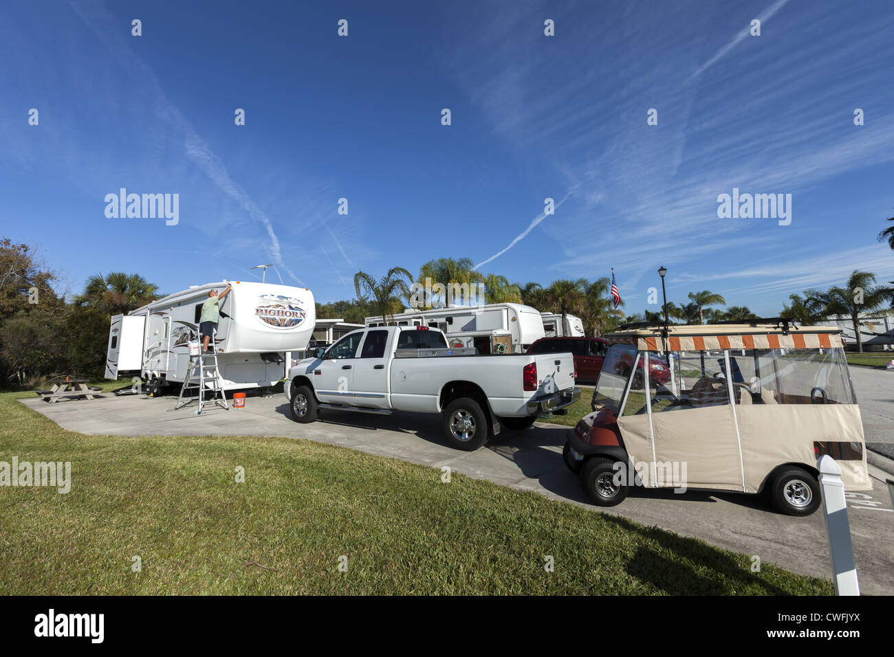 Man cleaning fifth-wheel Rv with one ton white dodge truck and golf cart - Stock Image