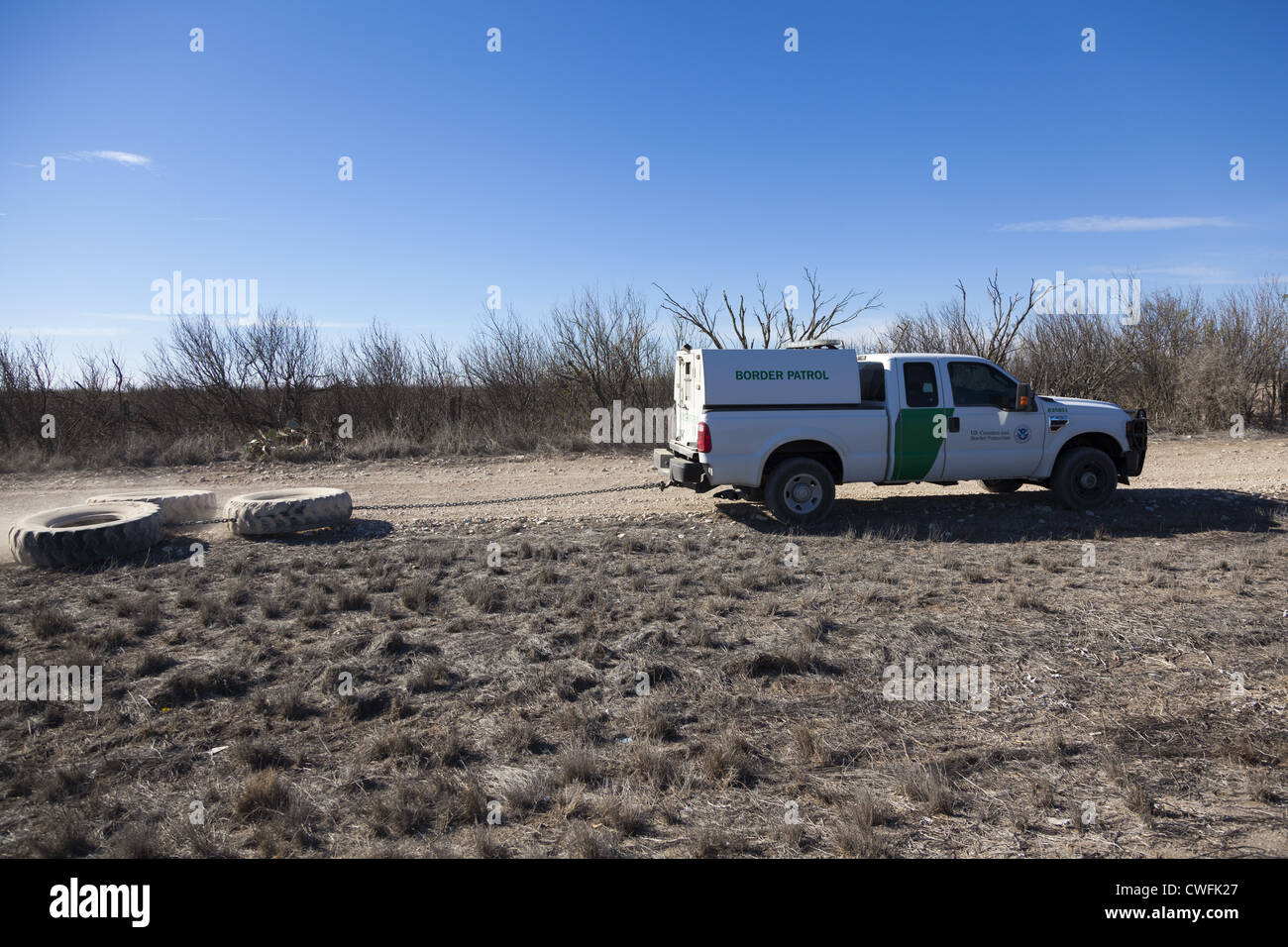 Border Patrol truck grading a trail alongside Highway 90 in Texas. This is to help spot illegals who may have crossed. - Stock Image