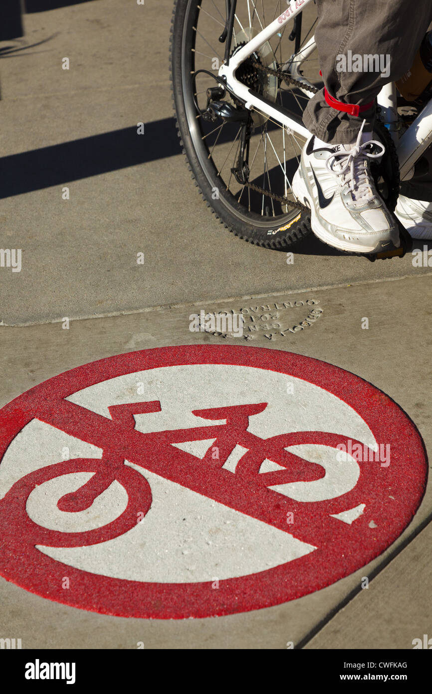 No cycling sign with bicycle and persons foot, shoe and part of leg - Stock Image