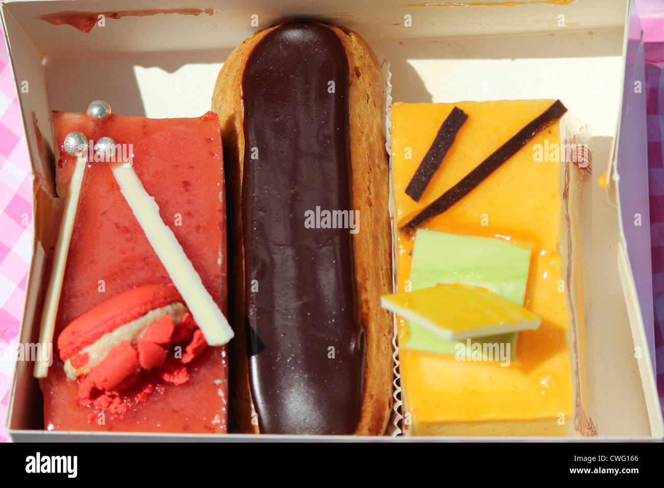Close-up of a Framboisine cake, an eclair, and a passion-fruit gateau - Stock Image