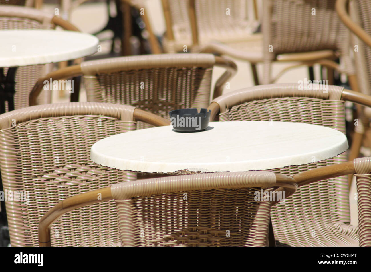 Ashtray on restaurant tables with wicker chairs outdoors. - Stock Image