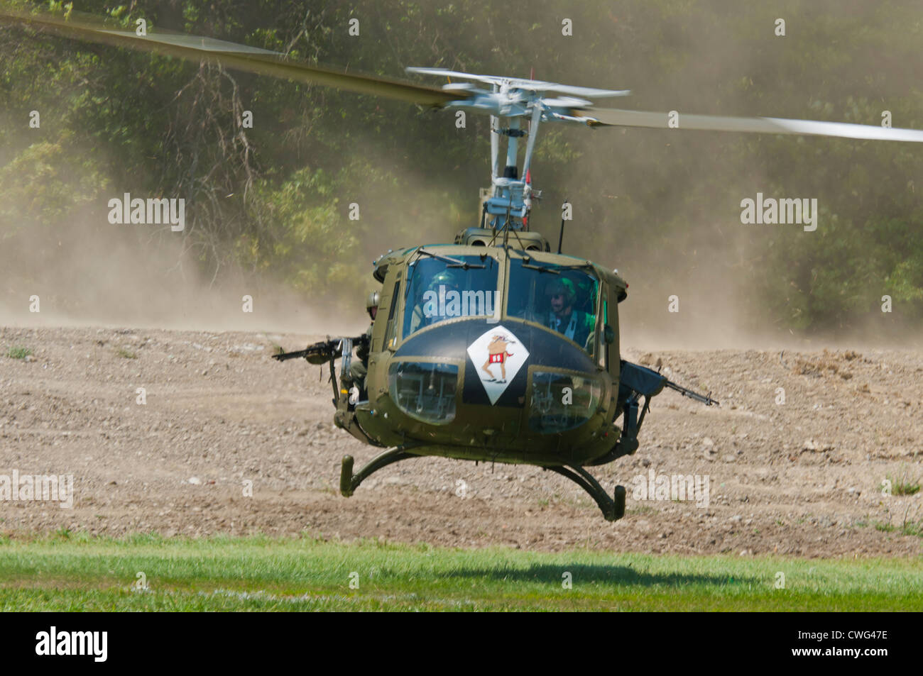 A restored Vietnam-era US Huey helicopter, equipped with an M60 MG, making a fast takeoff after dropping an infantry - Stock Image