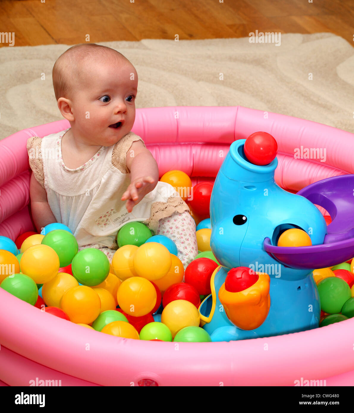 A 6 month old baby girl looks surprised as a ball pops out of the ...