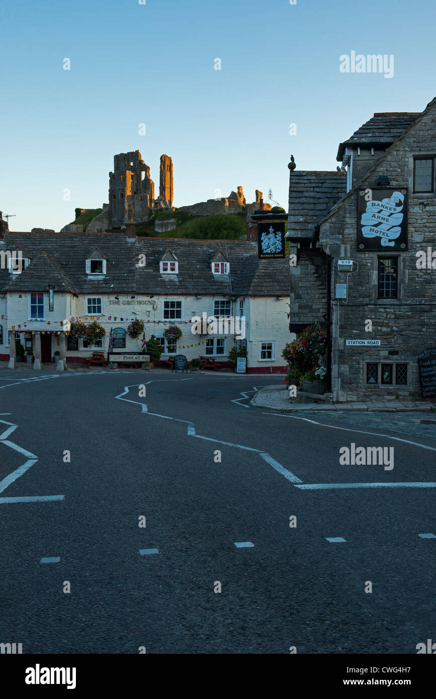 Corfe Castle lit by the rising Sun. The Greyhound Inn and Bankes Arms Corfe village Dorset England Stock Photo