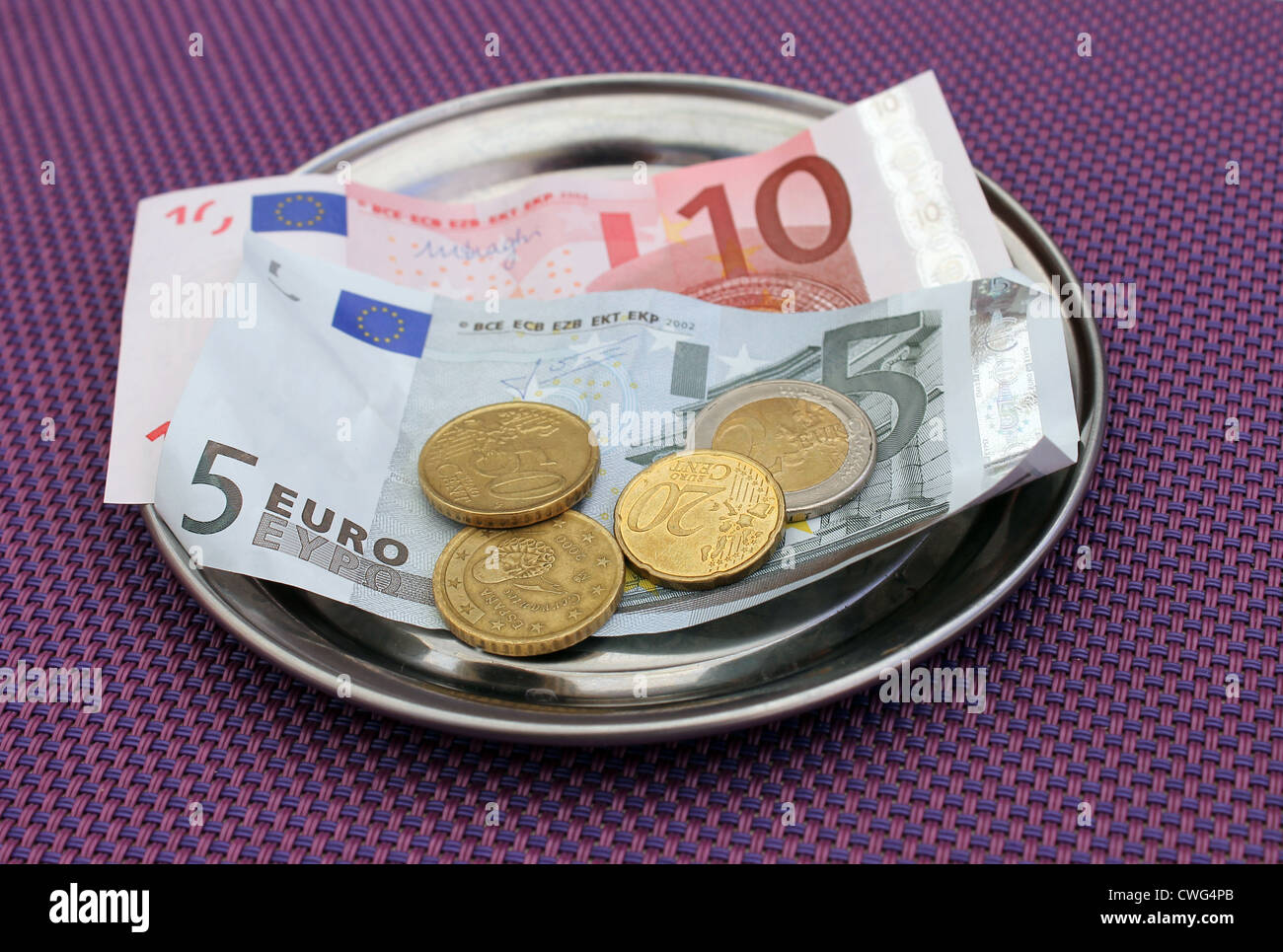 Euro tips and payment for bill on on restaurant table. - Stock Image