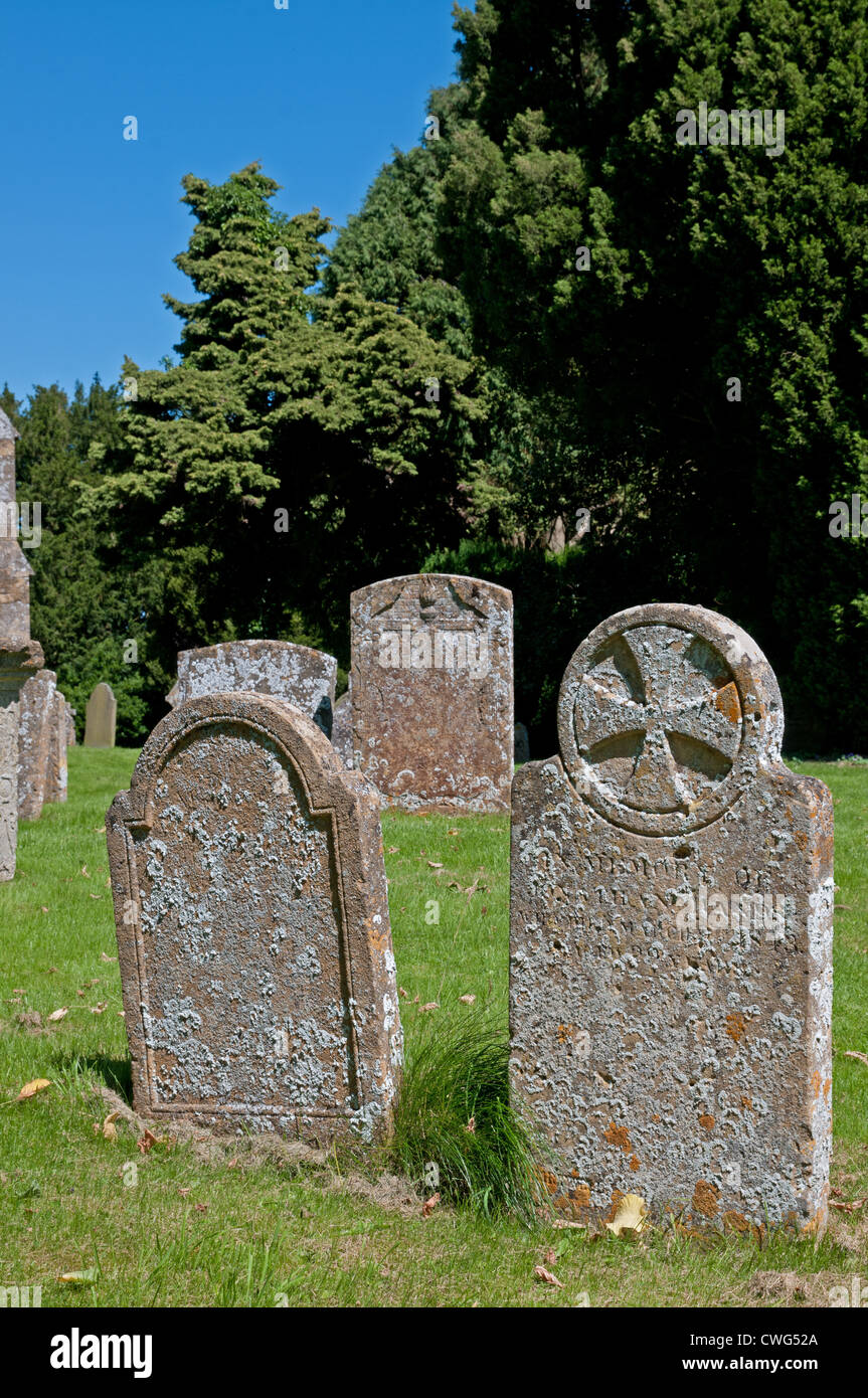 Ancient Grave stones with lichen and flared Christian Cross inside circle in St James Churchyard Chipping Campden - Stock Image