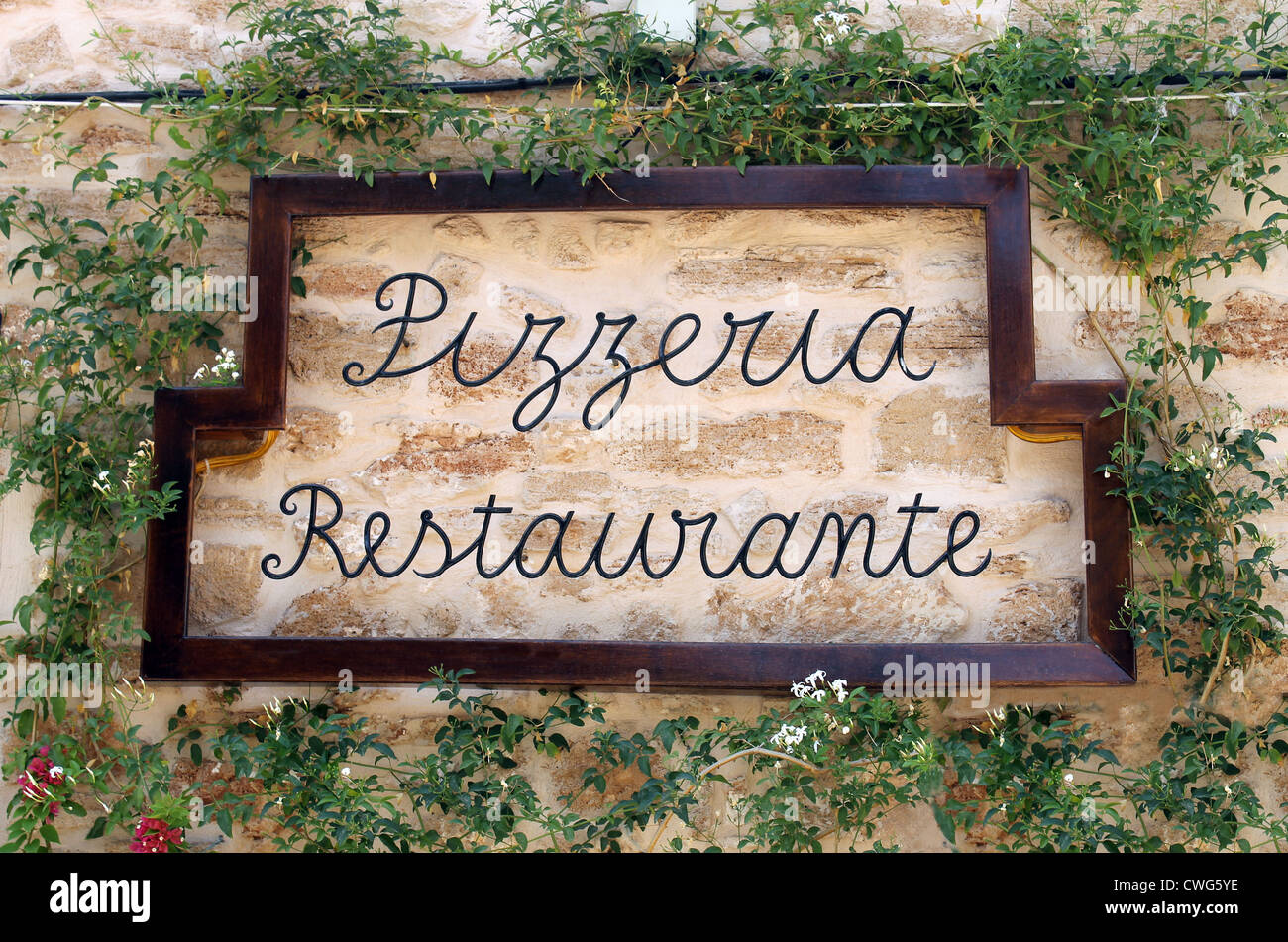 Pizzeria restuarant sign on old wall surrounded by ivy, Italian or Spanish. - Stock Image
