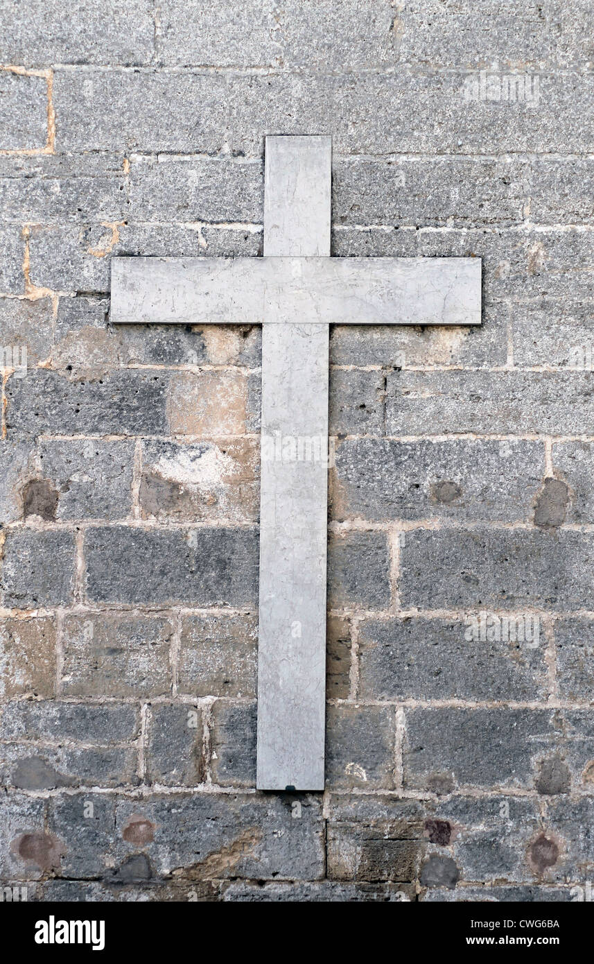 Old marble religious cross on gray or grey wall. - Stock Image