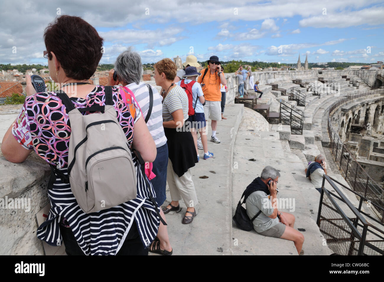 Tourists using mobile phones inside Roman amphitheatre or arena Nimes France showing obsession with modern communications - Stock Image