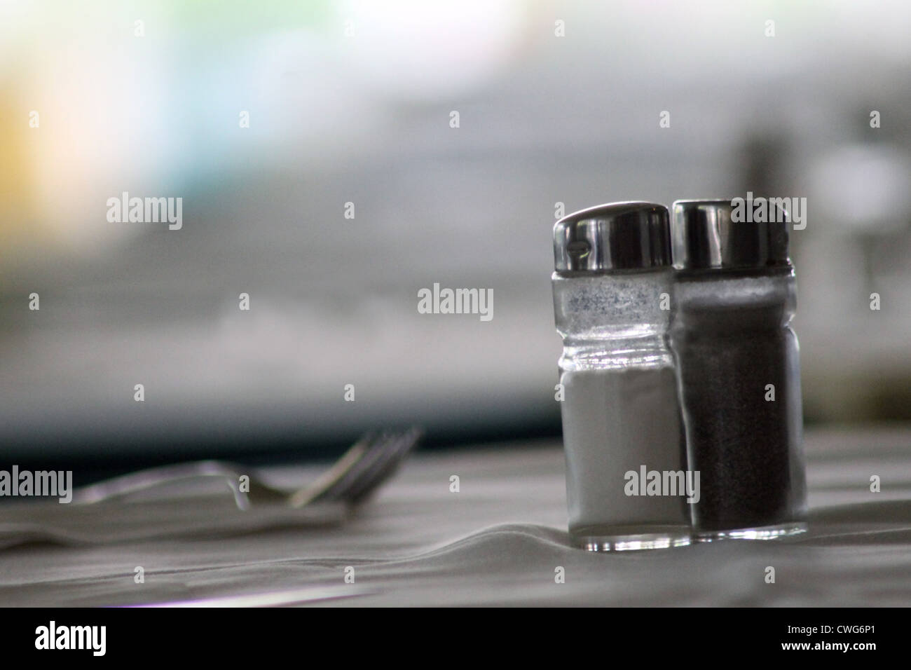 Salt and pepper shakers on table with fork and copy space, food and drink concept. - Stock Image
