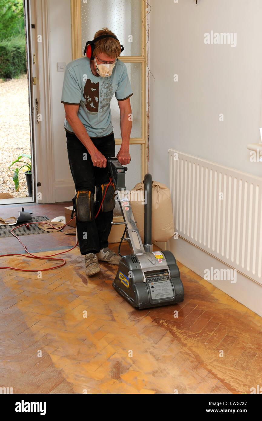 Man using floor sander on solid wooden parquet flooring - Stock Image