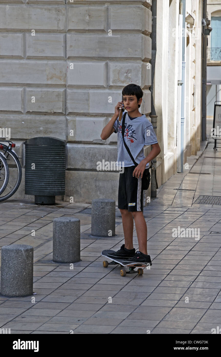 Young boy with skate board using mobile phone in Carree Square Nimes France - Stock Image