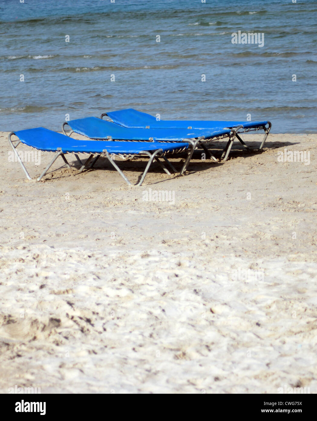 Sun loungers or beds on sandy beach in summer. - Stock Image