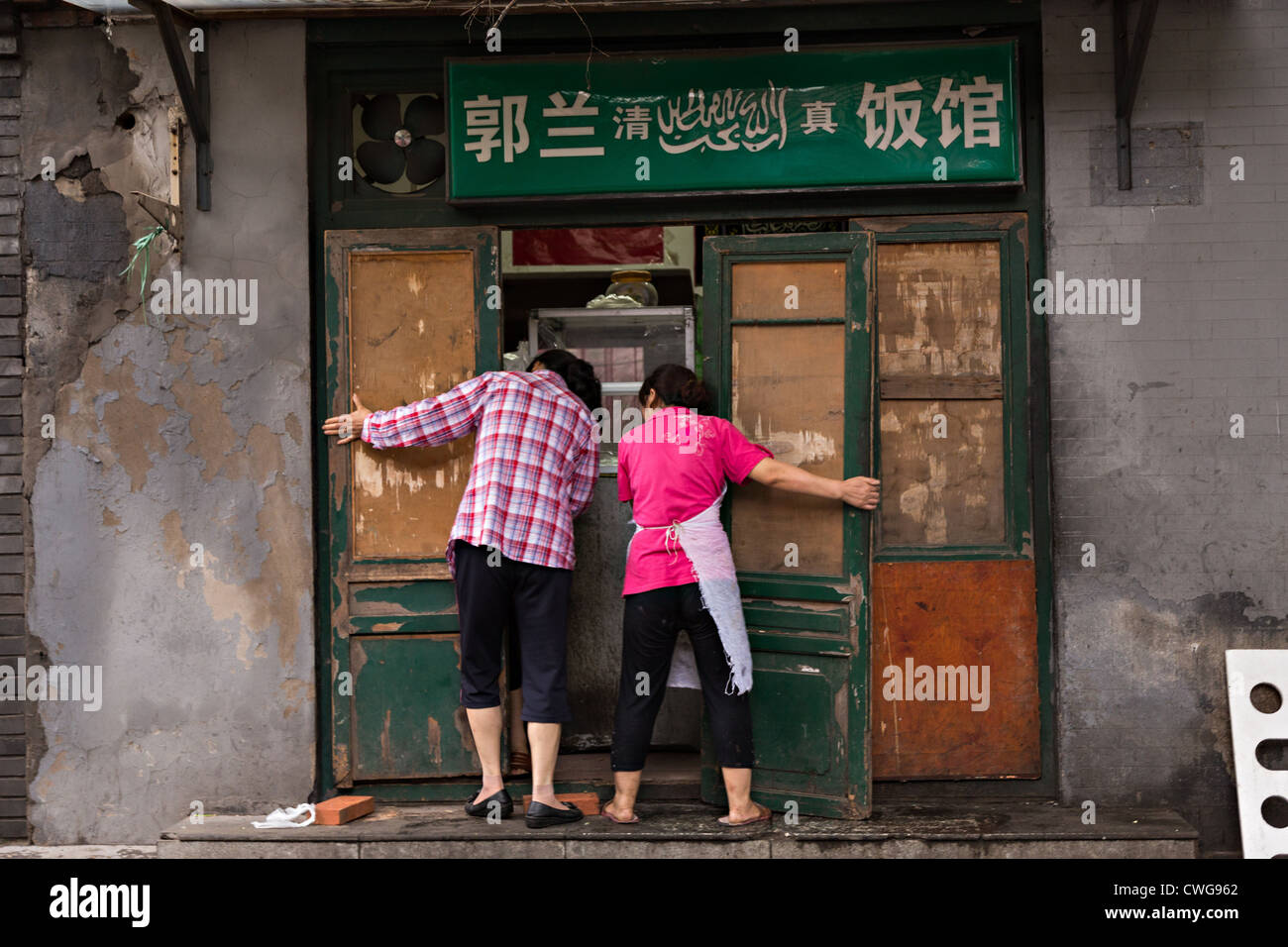 Two women close up their traditional shop along a hutong in Beijing, China - Stock Image