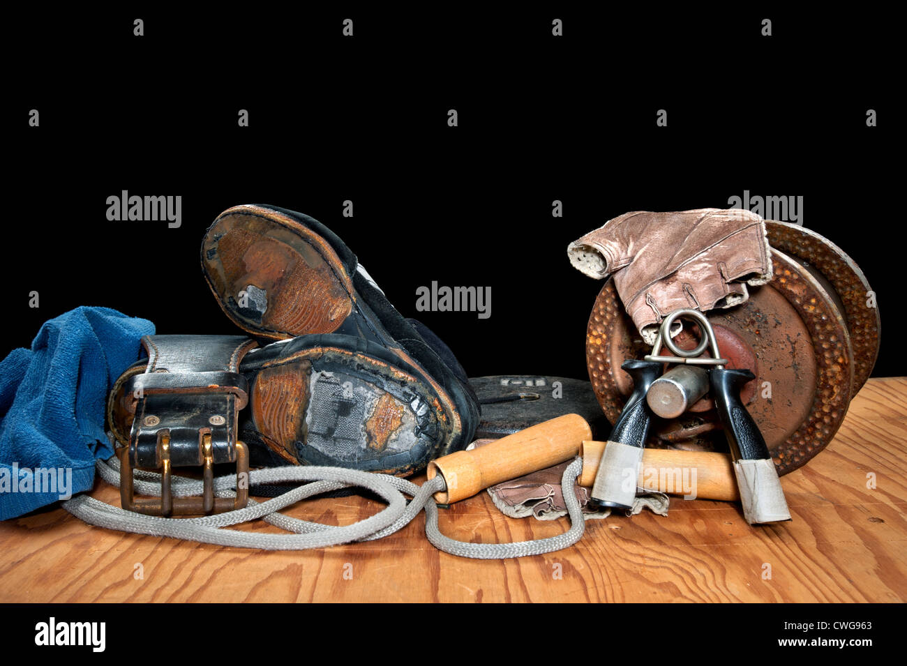 A collection of old exercise equipment including hand grips, dumbell, jump rope and old, torn weightlifting shoes. - Stock Image