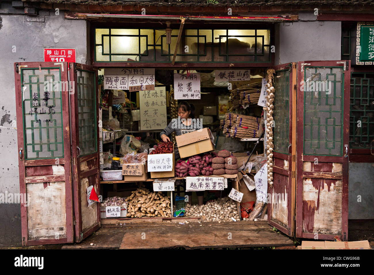 A woman works in her traditional shop selling root vegatables along a hutong in Beijing, China - Stock Image