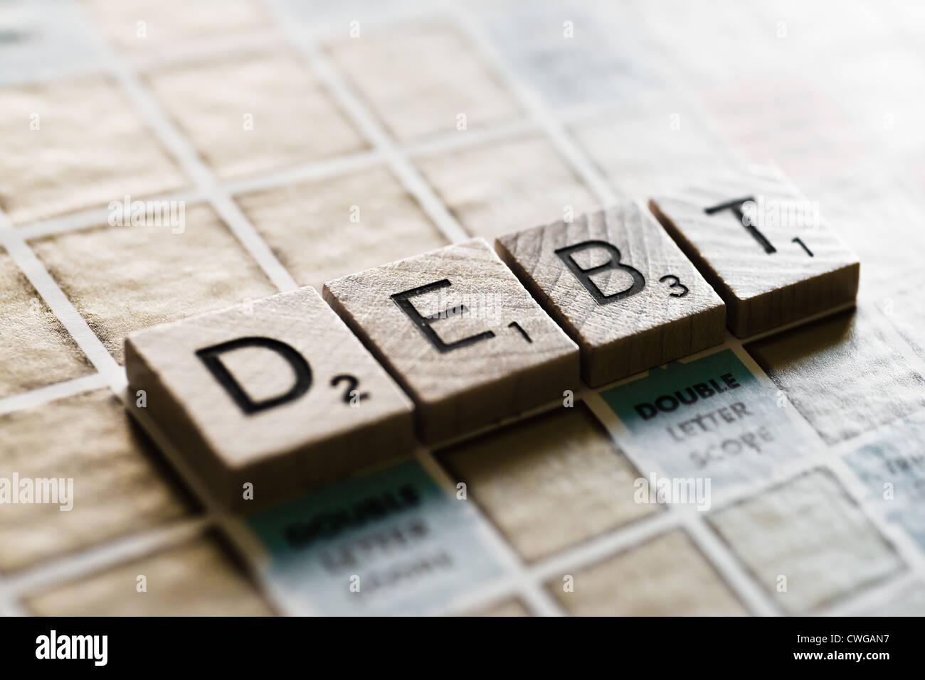 Letter tiles spelling the word DEBT Stock Photo