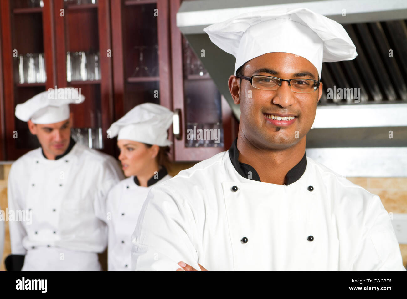 professional indian chef in kitchen with colleagues - Stock Image