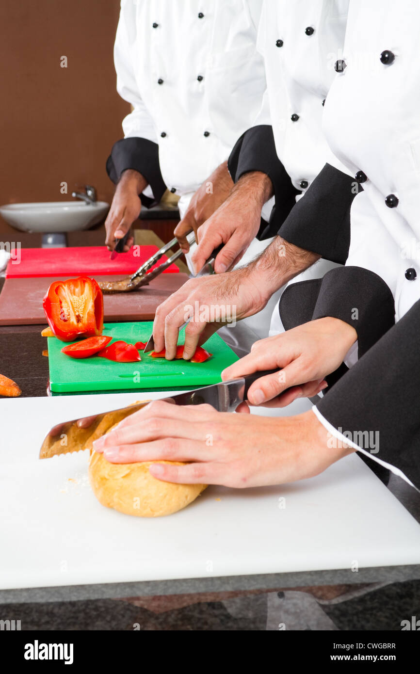 professional chefs cooking in restaurant kitchen - Stock Image